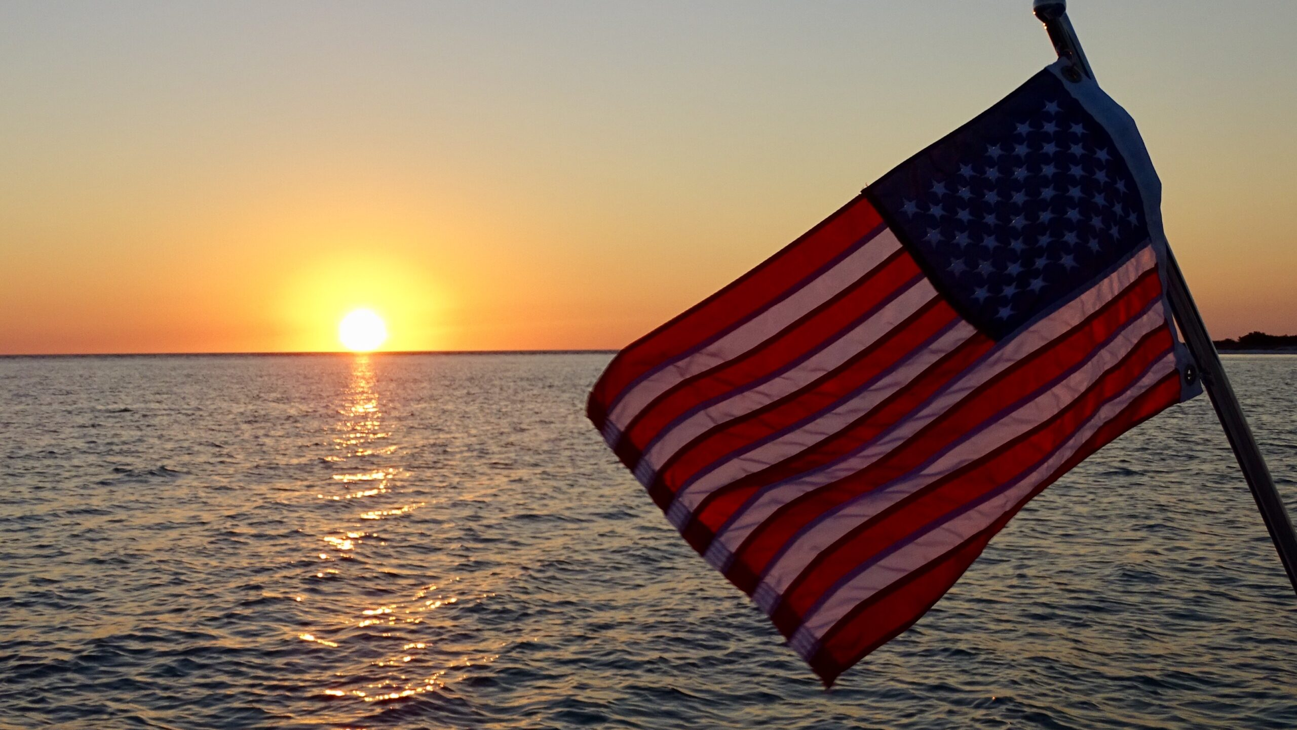 American flag over the sunset on Kokomo Charters